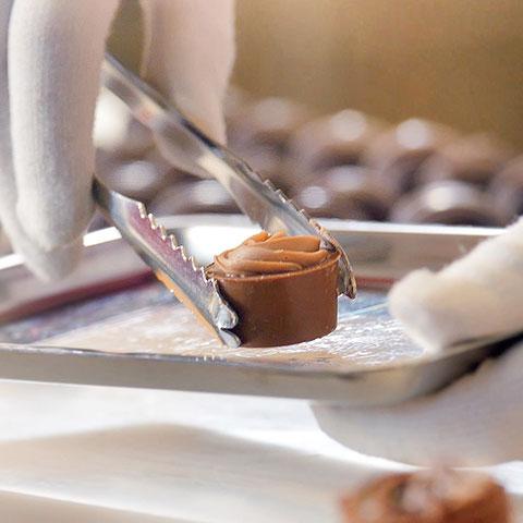 Nougat-Praline wird mit Zange auf Tablett gesetzt