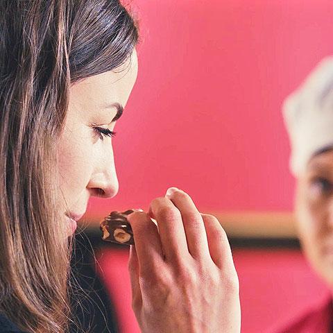 Frau riecht vor Verkostung an Schokoladenstück